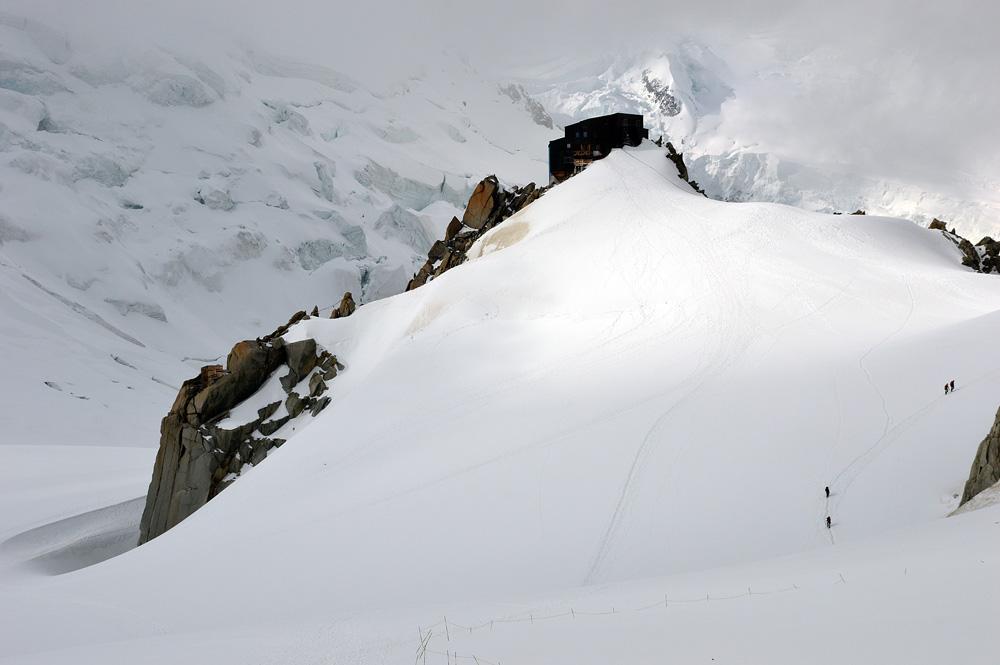 Abrigo Cosmiques. Note alguns escaladores seguindo pela direita, em direção ao Abrigo Simond.